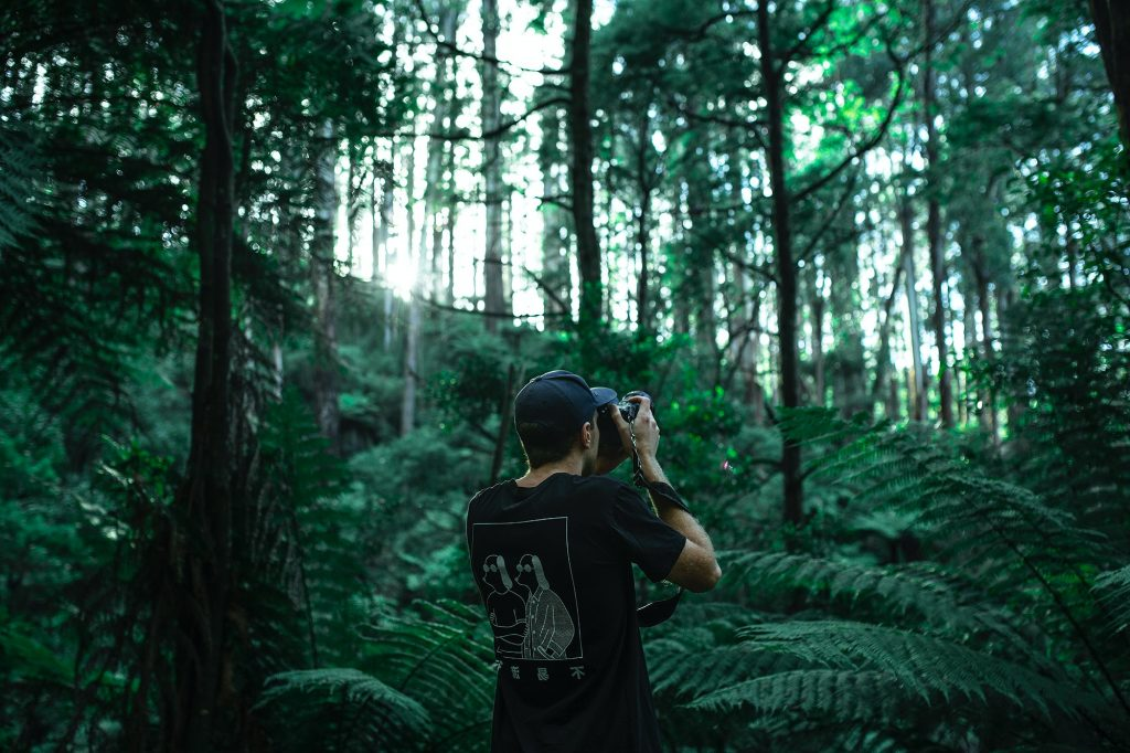 guy holding a camera in forest